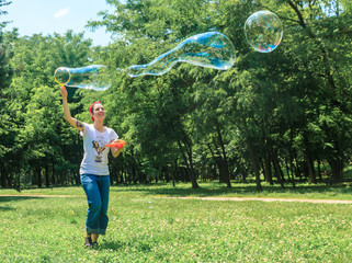 Happy young girl has fun with bubbles in a summer day in a park. She is smiling. She has tattoo and a vintage style with bandana and old school t-shirt
