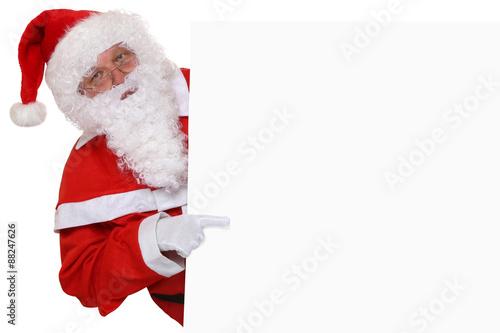 weihnachtsmann nikolaus zeigt an weihnachten auf schild. Black Bedroom Furniture Sets. Home Design Ideas