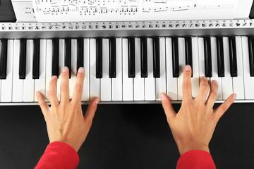 Woman playing synthesizer close up