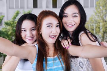 Three students taking photo at school