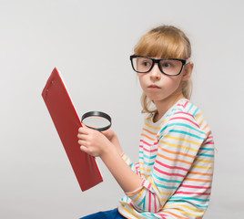 Little girl with a tablet and a magnifying glass