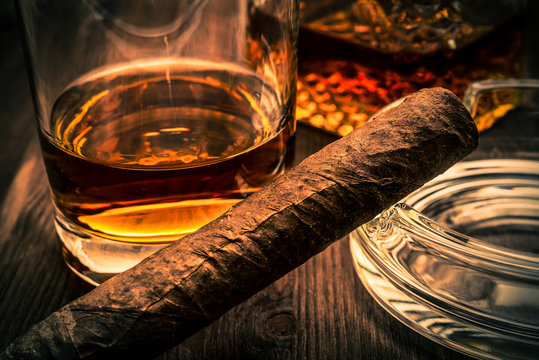 Decanter of whiskey and a glass with cuban cigar on a wooden table