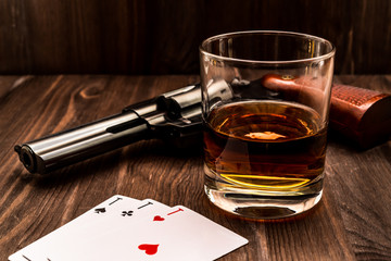 Fototapete - Glass of whiskey and playing cards with revolver on the wooden table