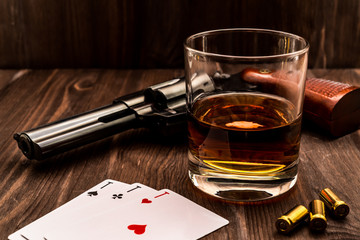 Wall Mural - Glass of whiskey and playing cards with revolver on the wooden table