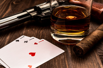 Wall Mural - Glass of whiskey and playing cards with revolver and cuban cigar on the wooden table