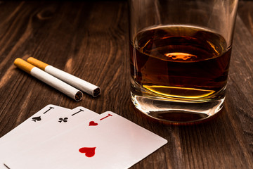 Wall Mural - Glass of whiskey and playing cards with two cigarettes on the wooden table