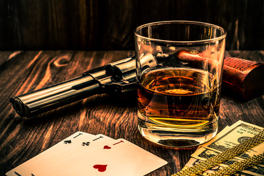 Glass of whiskey and playing cards with revolver and money on the wooden table