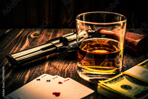 Fototapete Glass of whiskey and playing cards with revolver and money on the wooden table