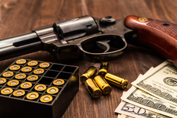 Revolver with cartridges and money on the wooden table