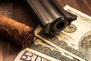 Barrel of a revolver with cuban cigar and money on the wooden table