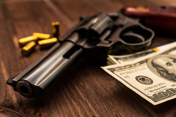 Revolver and pack of dollars with cartridges on the wooden table