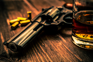 Wall Mural - Glass of whiskey with revolver on the wooden table