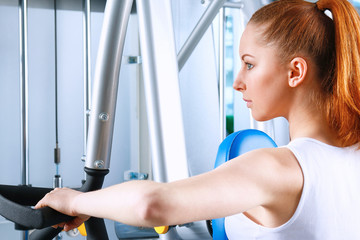 Beautiful girl at the gym exercising on trainers