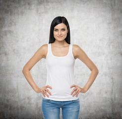Brunette woman is in a white tank top and blue denims. Concrete background.