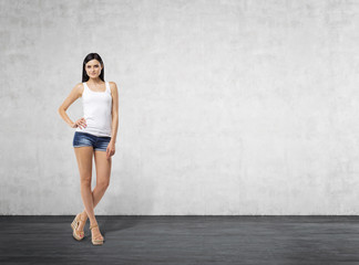 Full length portrait of a brunette woman who is in a white tank top and blue denim shorts. Room with the concrete wall.