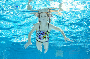 Child swims in pool underwater, happy active girl has fun in water, kid sport