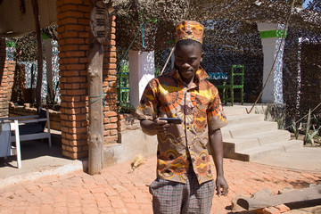 Portrait of a young African man looking at mobile phone..