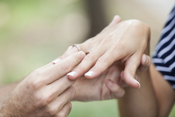 Boyfriend putting a engagement ring in his girlfriend finger outdoors