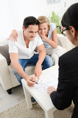 happy young couple at home with blueprint in discussion with a business woman