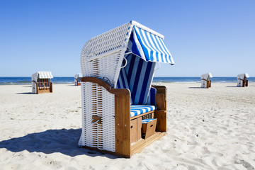 Wicker roofed beach chairs at the seashore