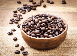 Coffee beans in wooden bowl on wooden background