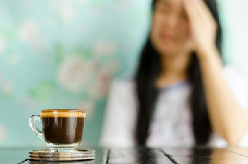 The woman,when not drink the cup of coffee, have a headache