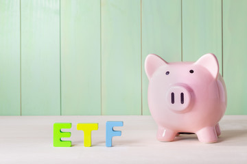 Exchange Traded Funds theme with wood block letters and piggy bank