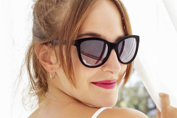 Close-up of smiling young woman with sunglasses that looks back while clutching white curtains viewed at backlighting