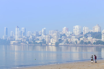 A Muslim and a Hindu man talking on Chowpatty beach with the skyscrapers of wealthy Malabar Hill behind, Mumbai, Maharashtra, India, Asia