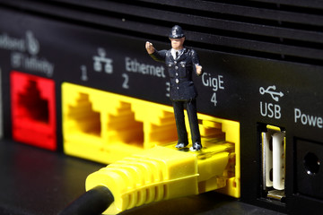 Miniature policeman router internet crime concept. Miniature scale model policeman standing on router representing internet crime.