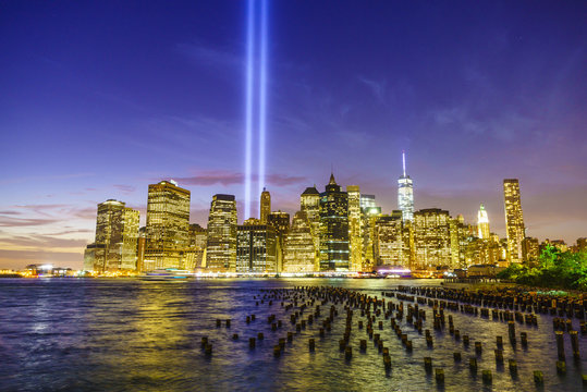 Lower Manhattan skyscrapers including One World Trade Center from across the East River at night, with light beams from the Tribute in Light 9/11 Memorial, New York City, New York