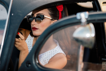 Beautiful pin-up girl inside vintage car putting makeup