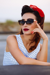 Pin-up poses with vintage sunglasses