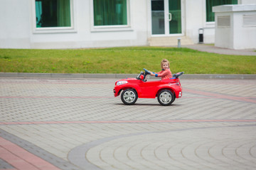Beautiful little girl riding toy car in summer park