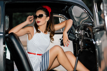 Beautiful pin-up girl inside vintage car