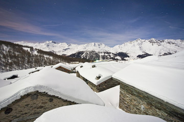 Group of mountain huts covered in snow under a starry night in Valle Spluga, Vachiavenna, Lombardy, Italy, Europe