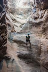 Woman rapelling down in slot canyon, canyoneering, Moab, Utah, United States of America, North America