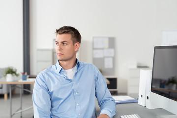 büroangestellter sitzt am schreibtisch