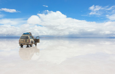 Car on the reflected surface of Salar de Uyuni lake in Bolivia