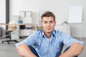 entspannter junger geschäftsmann im büro