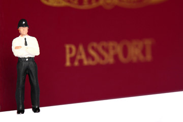 Miniature police officer passport. Miniature scale model police officer standing in front of a United Kingdom passport.
