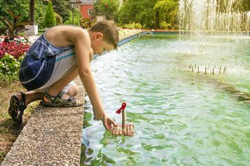 A child with a ship handmade near the fountain.