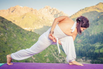 Inspired woman doing exercise of yoga at mountain range