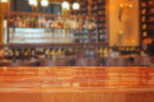 Wooden table over blurred bar interior