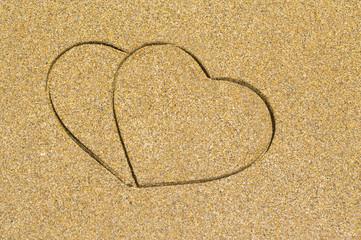 Two heart shape engraved in a wet sandy beach
