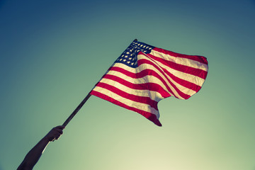 American flag with stars and stripes hold with hands against blu