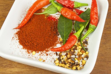 Spices in a ceramic bowl. Freshly picked chili peppers on a wooden table. Preparation for the domestic processing of a crop. Decoration of chilli peppers. Place for text menu. Healthy fresh food.