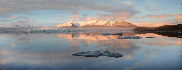 Panoramic view across the calm water of Jokulsarlon glacial lagoon towards snow-capped mountains and icebergs bathed in late afternoon light in winter, at the head of the Breidamerkurjokull Glacier on the edge of the Vatnajokull National Park, South Icela