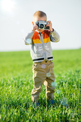 Little boy with an old camera shooting outdoor.