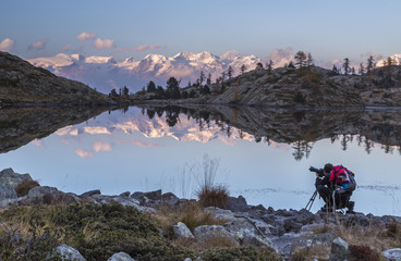 A panoramic view of the Alpine range overlooking the Mont Avic Natural Parc reflecting in a small lake in the Aosta Valley, Italy, Europe